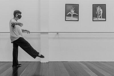 Bailarina treina, segurando a barra e elevando a perna direita. Na parede da academia dois quadros com fotos de bailarinos se apresentando