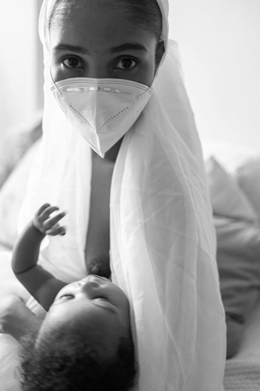 De máscara, mulher amamenta o bebê nos seus braços.